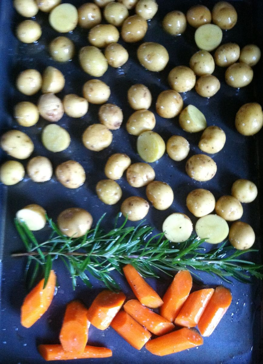 Carrots, rosemary, and potatoes go in first.